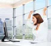business, triumph, people and education concept - happy businesswoman with computer and raised hands over office window background