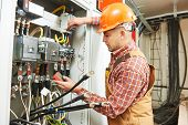 picture of fuse-box  - young adult electrician builder engineer worker in front of fuse switch board - JPG