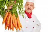Chef cook holding up a fresh bunch of carrots