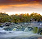 Evening landscape with waterfall on river