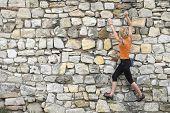 BELGRADE, SERBIA - JULY 29, 2014: young woman is training urban climbing on a wall of Kalemegdan Fortress in Belgrade. Shot in 2014