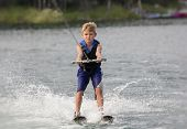 stock photo of ski boat  - Blonde Boy learning to waterski on a lake - JPG