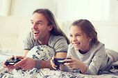 pic of morning  - Child playing video game on tv with father in morning at bed at home - JPG