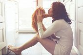 stock photo of domestic cat  - Young lady kissing cat on the floor at the kitchen at home - JPG