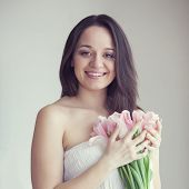 Portrait of woman holding bouquet of spring tulips