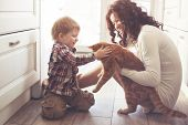 stock photo of joy  - Mother with her baby playing with pet on the floor at the kitchen at home - JPG