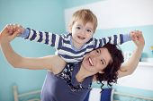 picture of little kids  - Young mother playing with her 2 years old little son at the bedroom - JPG
