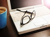 Cup of coffee and laptop with a pair of hipster glasses on wooden table