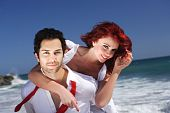 Young Couple At The Beach Giving Piggy Back