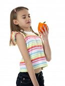 Cute young girl holding orange bell pepper, on white background.