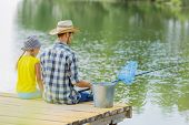 Rear view of father and daughter sitting on bridge and fishing