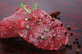 picture of peppercorns  - fresh raw beef fillet mignon on old retro style wood as background with rosemary peppercorn and salt - JPG