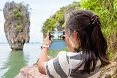 foto of james bond island  - Women tourist he is shooting a beautiful scenic view by mobile phone at Khao Tapu or James Bond Island in Ao Phang Nga Bay National Park Thailand - JPG