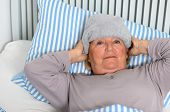 picture of forehead  - Sick Middle Aged Woman Lying Down on Bed with Towel on the Forehead While Looking up in Pensive Facial Expression - JPG