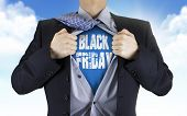 picture of friday  - businessman showing Black Friday words underneath his shirt over blue sky - JPG