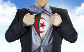 picture of algeria  - businessman showing Algeria flag underneath his shirt over blue sky - JPG