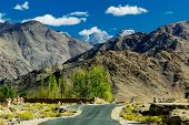 picture of jammu kashmir  - A concrete road towards beautiful rocky mountains and blue sky with peaks of Himalaya Leh Ladakh Jammu and Kashmir India - JPG