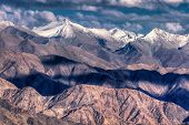 image of jammu kashmir  - Rocky landscape of with ice peaks in background blue sky with clouds Ladakh Jammu and Kashmir India - JPG