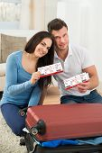 image of boarding pass  - Portrait Of Happy Young Couple Packing Luggage Showing Boarding Pass - JPG