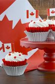 pic of flag confederate  - Happy Canada Day celebration cupcakes on red cake stand with red and white maple leaf flag against a rustic distressed wood background - JPG