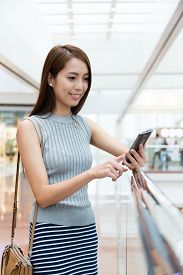 foto of status  - Asian woman using the cellphone for upload the status at shopping mall - JPG