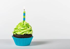 foto of icing  - Chocolate Cupcake decorated with green icing sprinkles and a lit birthday candle on a white background - JPG