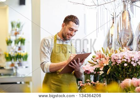 people, sale, retail, business and floristry concept - happy smiling florist man with clipboard writ