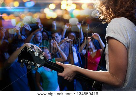 holidays, music, nightlife and people concept - close up of singer playing electric guitar and singi