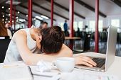 Exhausted fatigued young business woman sleeping on table with laptop at workplace poster