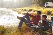 Father and son on a camping trip fishing by a lake poster