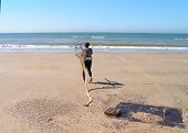 foto of clam digging  - spanish clam gatherer on the beach going to the ocean
