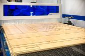 Modern Cnc Machining Center For Cutting A Plywood Sheet. The Machine Cuts Out Parts From A Chipboard poster