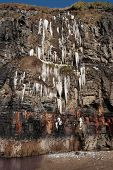 Melting Cascade Of Icicles On A Cliff Face