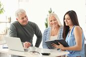 Mature couple discussing pension plan with consultant in office poster