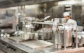 Defocused Chef Preparing Food In Commercial Stainless Steel Kitchen In Restaurant poster
