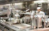 Defocused Chef Preparing Food In Commercial Stainless Steel Kitchen In Restaurant poster