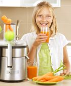 Fresh fruit juice making. Happy Girl drinking fresh carrot and apple juice in the kitchen. Juice Ext