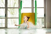 Little girl sliding down the water slide and splashing the water. Water park. Aquatic activity. poster