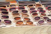 Sunglasses In A Wooden Frame. Many Sunglasses. Designer Glasses. poster