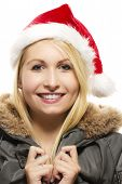 beautiful laughing blonde woman in a parka wearing santa's hat