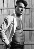 Sexy Serious Sensual Muscular Young Macho Man With Bare Torso In White Shirt Standing Indoor On Wood poster