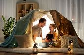 family, hygge and technology concept - happy father and little daughter with tablet pc computer in k poster