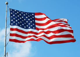 foto of waving american flag  - An American flag flying in the wind against a blue sky - JPG