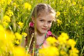 Menina sentada na grama e flores