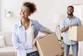 Moving New Home. Happy Black Spouses Carrying Packed Boxes Into Own Apartment. Selective Focus poster