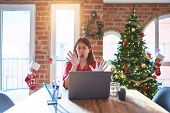 Beautiful woman sitting at the table working with laptop at home around christmas tree afraid and te poster