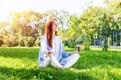Young Redhead Woman Meditating In Lotus Pose With Cup Of Coffee On Green Grass. Beautiful Calm Girl  poster