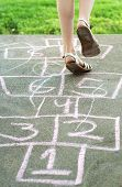 image of hopscotch  - Little girl playing hopscotch in backyard with pink numbers - JPG