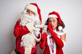 Senior couple wearing Santa Claus costume holding dollars over isolated white background hand on mou poster