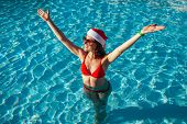 New Year And Christmas Holiday. Woman In Santas Hat And Bikini Raising Arms In Swimming Pool. Tropic poster